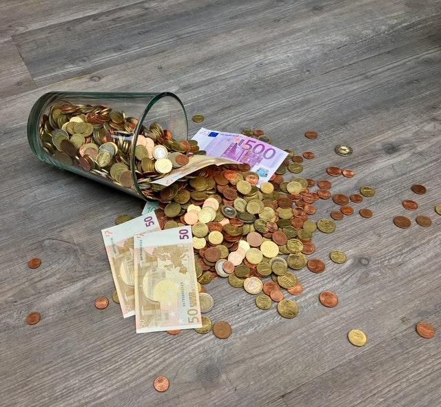 sklenice plná mincí, bankovky